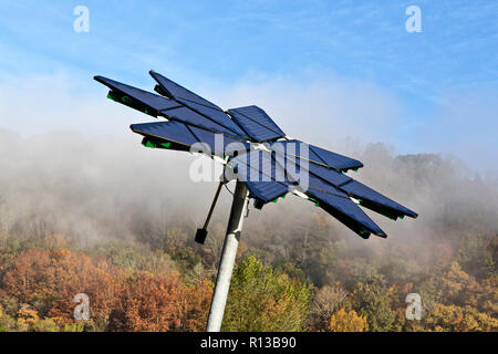 Solar array identified as  'Solar Photovoltaic Flair',  facilitates electric vehicle charging station, dissipating morning fog. - Stock Photo