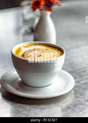 Casual Coffee shop. Latte art. Foaming latte. Water jug in clear glass. orange flowers in a white oval white vase. - Stock Photo