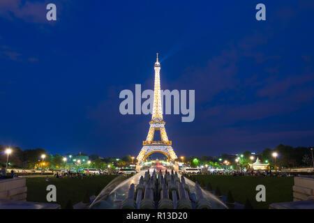 PARIS, FRANCE - May 8, 2016:  Tourist sightseeing beautiful night scene of illuminated Eiffel Tower at dusk, Paris, France. - Stock Photo
