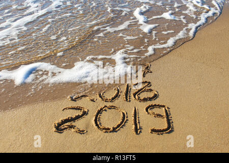 2019, 2018 and 2017 years written on sandy beach sea. Wave washes away 2017, 2018. - Stock Photo