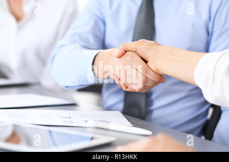 Close-up of business handshake at meeting or negotiation above the desk in office. Partners shaking hands while satisfied because signing contract or financial papers.  Success concept - Stock Photo