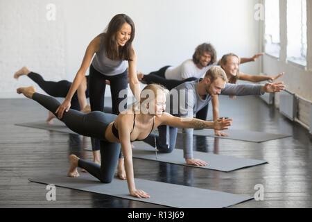 Young female yoga instructor teaching Bird dog pose - Stock Photo