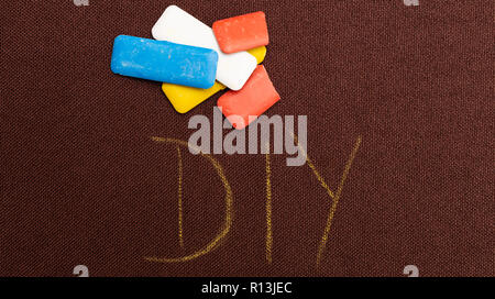 DIY as do it yourself concept being written on brown material with coloured tailoring chalk above - Stock Photo