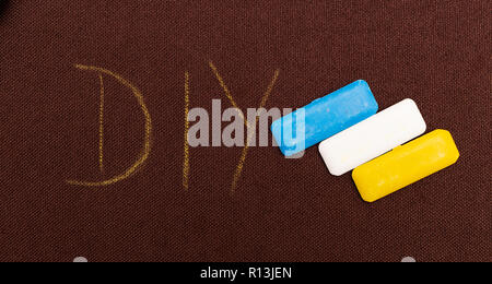 DIY as do it yourself concept written on brown fabric as background next to coloured tailoring chalk - Stock Photo