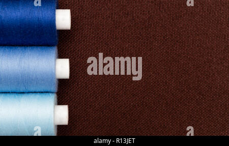 Copyspace for advertising on brown fabric with shades of blue thread bobbins as sewing concept - Stock Photo