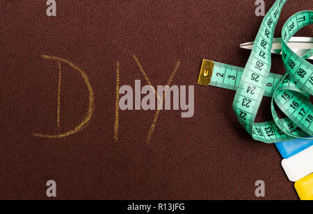 DIY text as do it yourself or handmade concept written on brown fabric as background with scissors, measuring tap and chalk - Stock Photo
