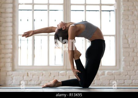 Young sporty yogi woman practicing yoga, doing Camel pose - Stock Photo