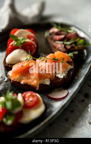 Sandwiches with roast beef and arugula, salmon and cumin, mozzarella and tomatoes on brown bread at gray plate - Stock Photo