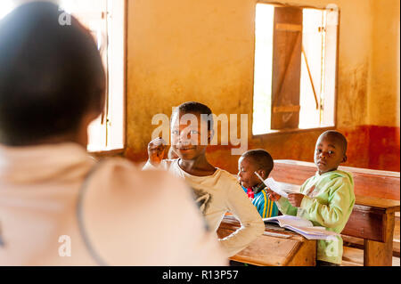 Bafoussam, Cameroon - 06 august 2018:  smiling school girl during lesson in village school talking with teacher - Stock Photo