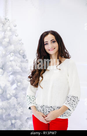 Gorgeous brunette woman posing in decorated studio against Christmas tree. - Stock Photo