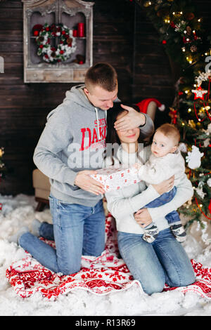 Happy family opening christmas presents with children. - Stock Photo