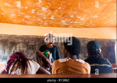 Bafoussam, Cameroon - 06 august 2018: young african woman teacher volunteer smiling during lesson in humble school classroom
