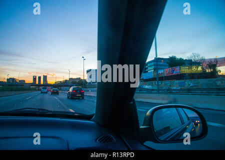 Cuatro Torres and A-1 motorway at dusk, view from inside a car. Madrid, Spain. - Stock Photo