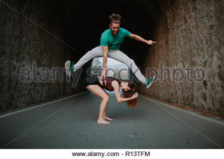 A young couple doing action shots in the street - Stock Photo