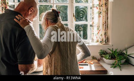 Rear view of a senior couple standing together in kitchen cooking food. Elderly woman watching her husband cook food standing in kitchen. - Stock Photo