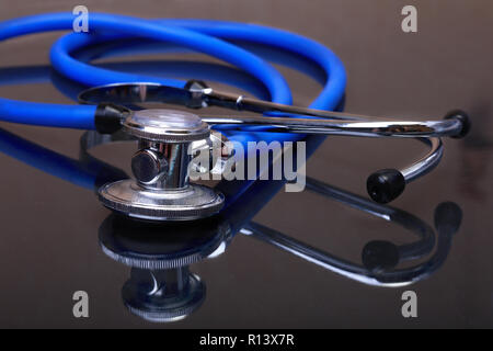Medical stethoscope isolated on dark mirror background - Stock Photo