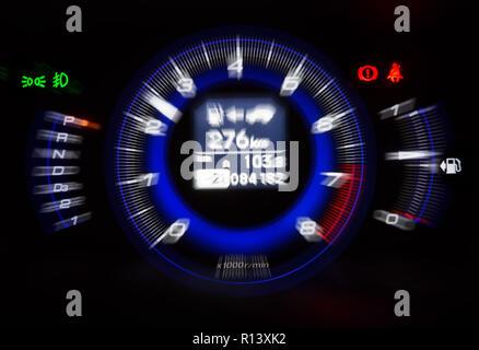 Closeup modern automotive tachometer on black background, motion blur filter effect - Stock Photo