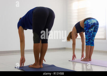 Couple of yogis in uttanasana. Young man and woman practicing standing forward bend yoga pose in bright studio. Exercise, flexibility, workout concept