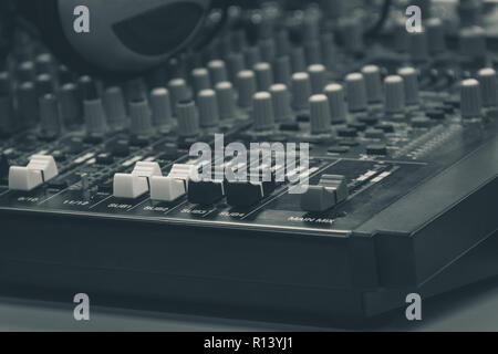 Professional audio mixer and headphones. Mixing desk, sound board. Closeup on controls and equalizers. Film and music studio recording equipment - Stock Photo