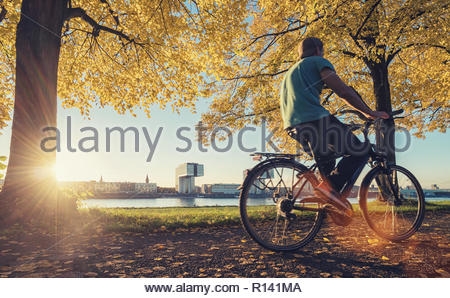 A man riding a bicycle in the park - Stock Photo