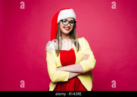 Smiling cheerful pretty girl in cat-eye glasses and santa hat. - Stock Photo