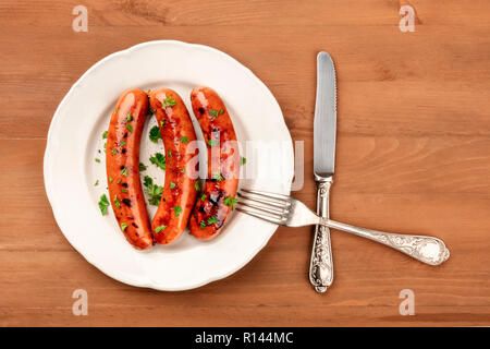 A photo of a plate of fried sausages with a fork and a knife, shot from above on a rustic wooden background with a place for text - Stock Photo