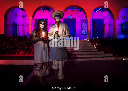Merida, Cementerio General, Mexico - 31 October 2018: Customed man and woman with with mexican traditional white clothes and scarves and skull make-up - Stock Photo