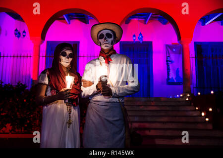 Merida, Cementerio General, Mexico - 31 October 2018: Close up of customed man and woman with with mexican traditional white clothes and skull make-up - Stock Photo