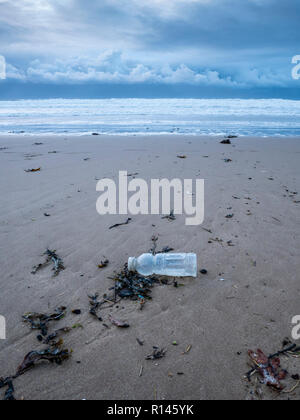 A discarded plastic bottle on a beach in the UK part of the plastic pollution and environmental problem - Stock Photo
