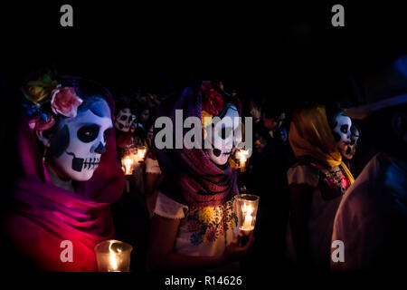 Merida, Cementerio General, Mexico - 31 October 2018: Three women with Catrina customes, scarves on their head and flowers in the hair with skull make - Stock Photo
