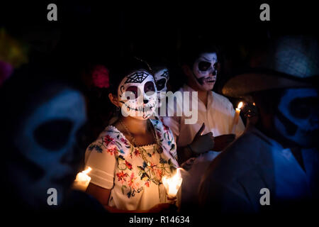 Merida, Cementerio General, Mexico - 31 October 2018: Woman with skull and spiderweb make-up and dress with traditional mexican flowers surrounded by  - Stock Photo