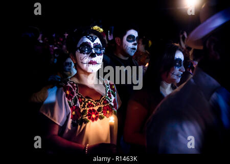 Merida, Cementerio General, Mexico - 31 October 2018: Woman with skull and spiderweb make-up and glasses and dress with traditional mexican flowers su - Stock Photo
