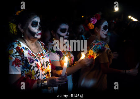 Merida, Cementerio General, Mexico - 31 October 2018: Three customed woman dressed as Catrinas with skull make-up having troubles with the candles bet - Stock Photo