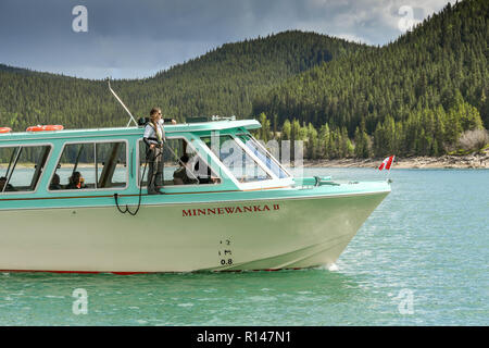 BANFF, AB, CANADA - JUNE 2018: Scenic view of a small tourist sightseeing boat on Lake Minnewanka near Banff. A member of the crew is standing on the  - Stock Photo