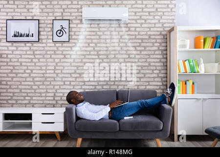 Happy Young African Man Using Laptop Enjoying Cooling Under Air Conditioner At Home - Stock Photo