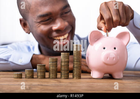 Happy African Man Inserting Coin In Piggybank Near Stack Of Coins - Stock Photo
