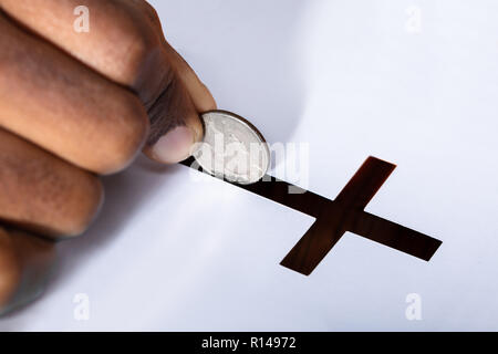 Close-up Of A Person's Hand Inserting Coin In Crucifix Slot - Stock Photo