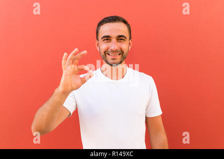 Picture of happy young handsome man standing isolated over red wall background. Looking camera showing okay gesture. - Stock Photo