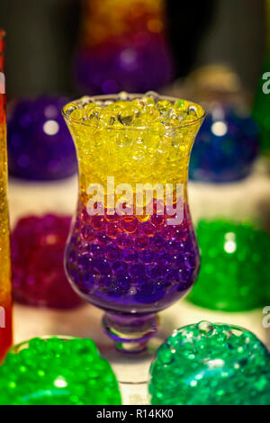 Glass cup with a hydrogel of bright, colorful color - Stock Photo