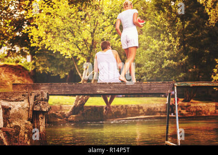 couple in love enjoying watermelon while sitting on the wooden bridge over the river in beautiful nature - Stock Photo