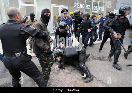 April 28, 2014 - Donetsk, Ukraine: An Ukrainian riot police officer dives on a pro-Ukraine demonstrator in order to protect him from his pro-Russia aggressors.Pro-Russia militants attacked Ukrainians who demonstrated peacefully for the preservation of the unity of their country. The pro-Russian separatist group, mostly youths in balaclava, then celebrated their actions by screaming they had smashed 'the fascists'. Une manifestation pacifique en faveur de l'unite de l'Ukraine a Donetsk est brutalement dispersee par des groupes separatistes pro-russes armes de batons et, pour certains, d'armes b - Stock Photo