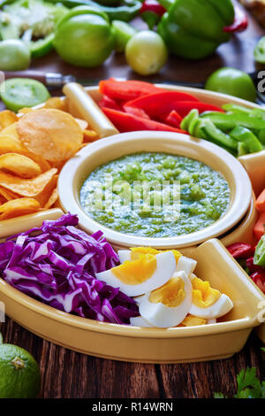 mexican set of chopped fresh vegetables with green salsa verde, hard boiled eggs and chips in bowls on old rustic wooden board with ingredients, verti - Stock Photo