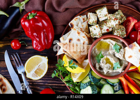 overhead view of a platter with vegetables and baba ganoush dip. ingredients: eggplant, lemon, tomatoes, pita bread on an old wooden table with knife  - Stock Photo