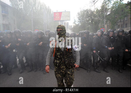 April 28, 2014 - Donetsk, Ukraine: A pro-Russia separatist leader confronts a squadron of Ukrainian riot police trying to protect a peaceful demonstration of Ukrainians in favor of the unity of their country. Fear is visible on the face of the police officers because they know there are hundreds more violent separatists in the streets nearby. Despite police protection, the pro-Russia group violently attacked and dispersed the peaceful demonstrators.The pro-Russian separatist group, mostly youths in balaclava, then celebrated their actions by screaming they had smashed 'the fascists'. Une manif - Stock Photo