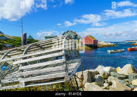 View of lobster traps, boats and houses, in the fishing village Peggys Cove, Nova Scotia, Canada - Stock Photo