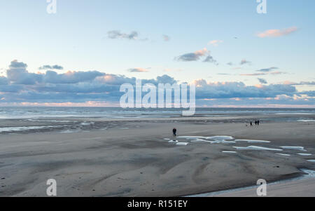Unrecognizable tourists stroll on Blackpool Beach at sunset during an autumn weekend in late October 2018. Blackpool is one of Englands favorite seasi - Stock Photo