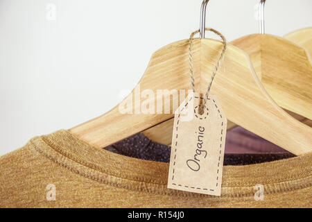 Organic clothes. Natural colored t-shirts hanging on wooden hangers in a row. - Stock Photo