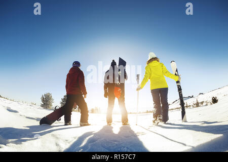 Three friends skiers and snowboarders stands with ski equipment. Ski resort concept - Stock Photo