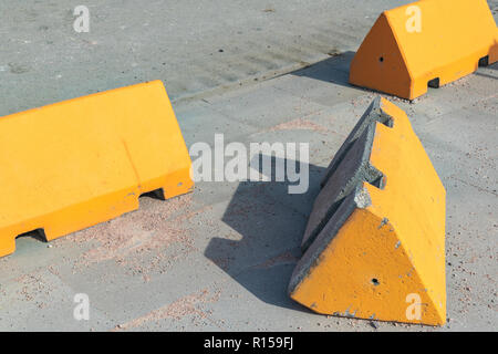 Concrete anti-terrorism barriers on a sidewalk alongside an asphalt street with one lying on its side. - Stock Photo