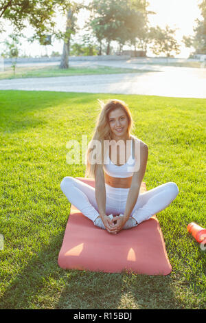 Sport girl siting on a grass after exercises - Stock Photo